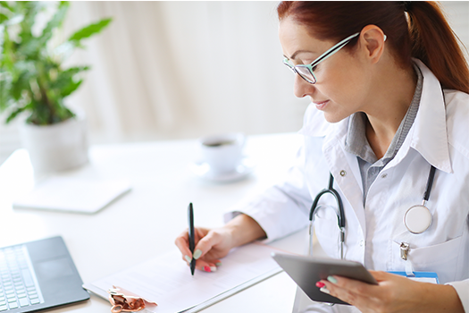 Smiling doctor using tablet in medical office